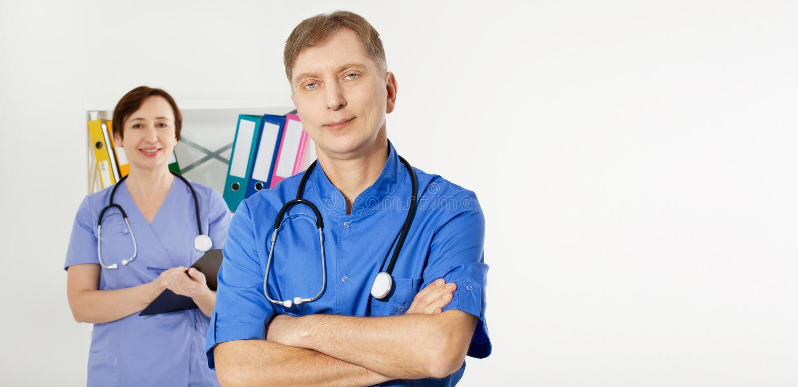 Male doctor with crossed arms and female doctor with folder in medical office, medical insurance, copy space, selective focus stock photo