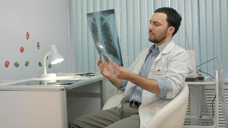 Male doctor or dentist looking at x-ray. People. Professional shot in 4K resolution. You can use it e.g. in your commercial video, business, presentation royalty free stock image