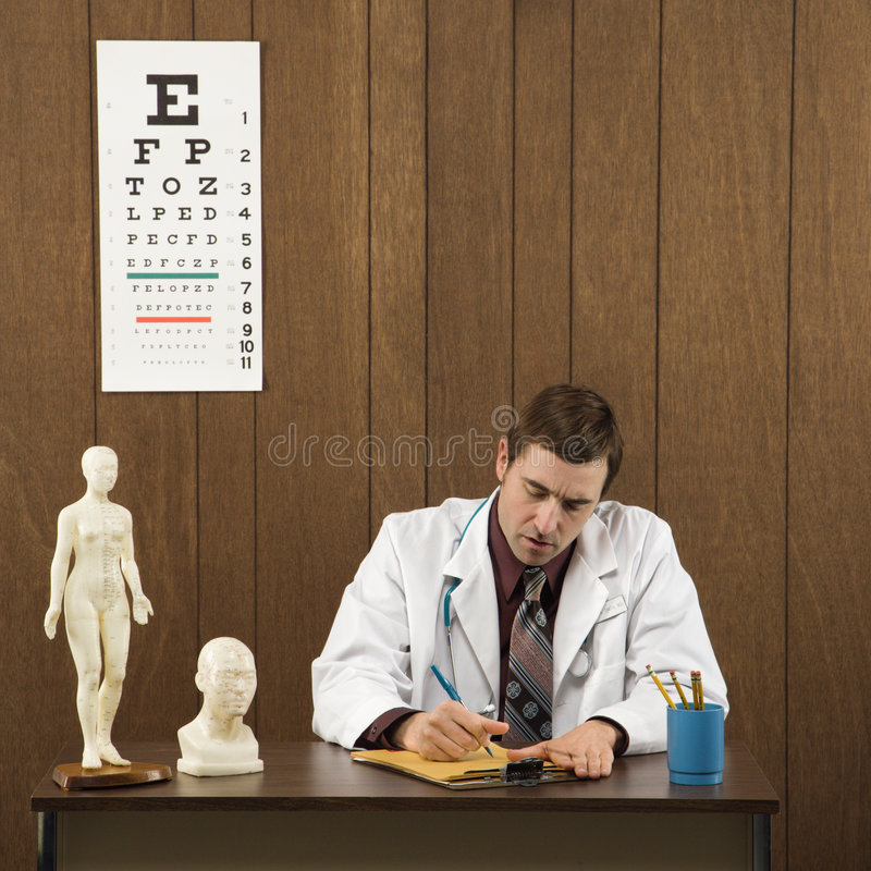 Download Male Doctor At Desk Writing. Stock Image - Image of 061214d0106, adult: 2052065
