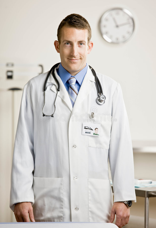 Male doctor in exam room. Confident doctor in lab coat and stethoscope standing in doctor�s office stock photography