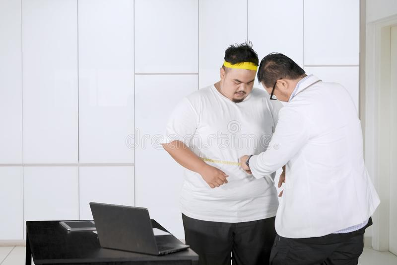 Male doctor examines fat belly of his patient royalty free stock image