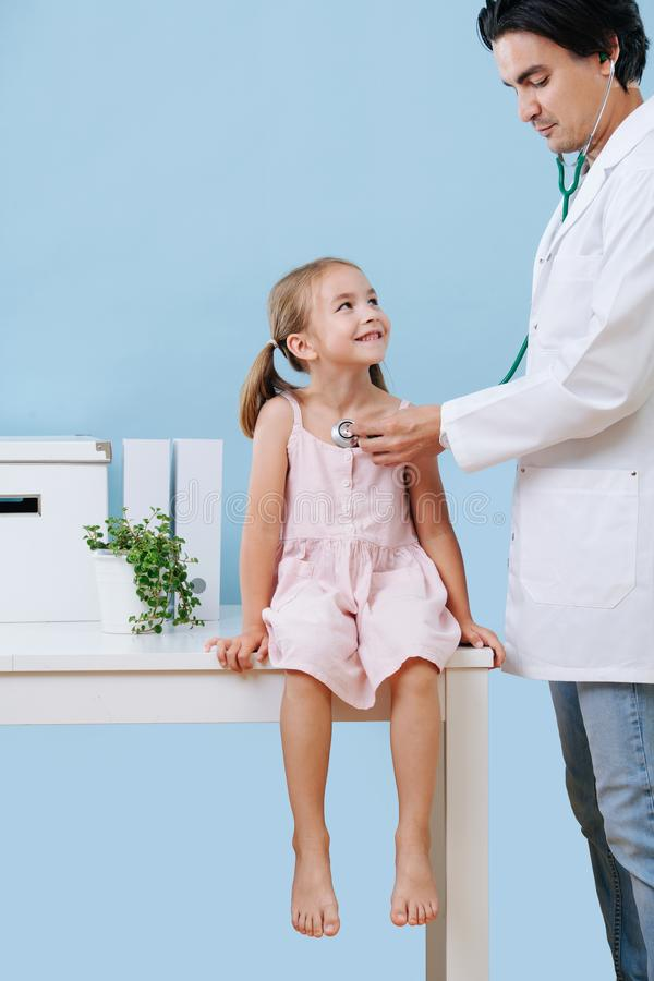 Male doctor examining a cheerful child girl, that sits on a table in a hospital royalty free stock photography