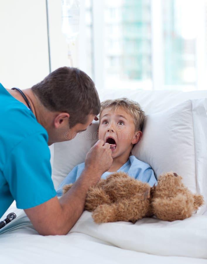 Male doctor examining child throat
