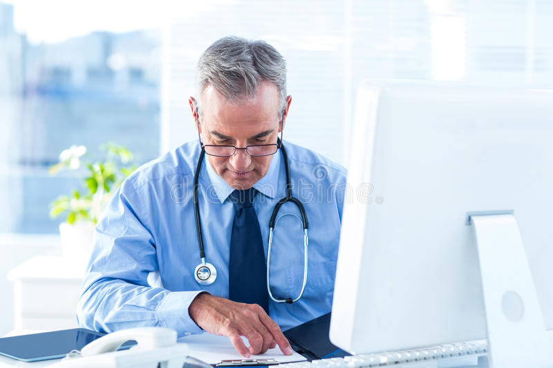 Male doctor examining document in hospital stock photo