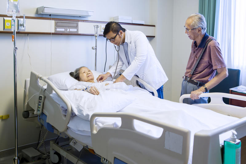 Male doctor examining senior patient stock images