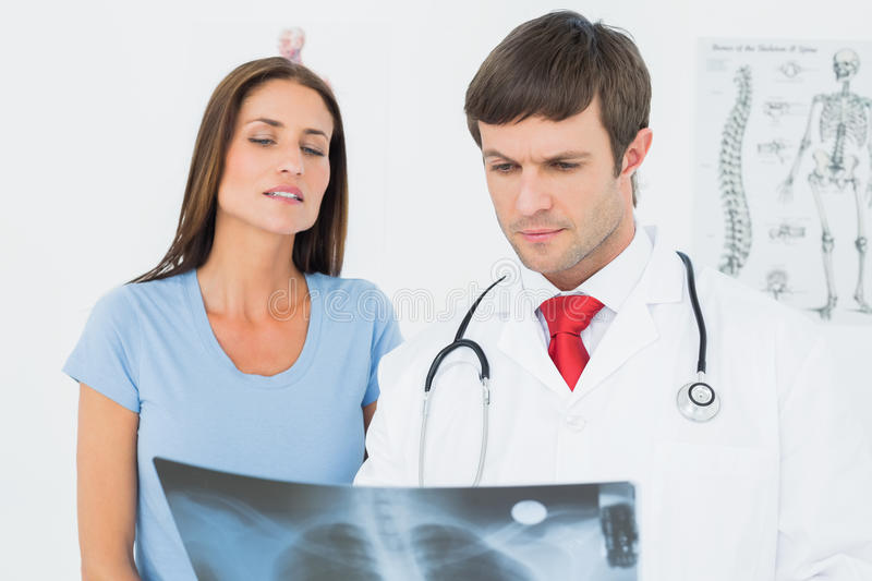 Male doctor explaining lungs xray to female patient royalty free stock photos