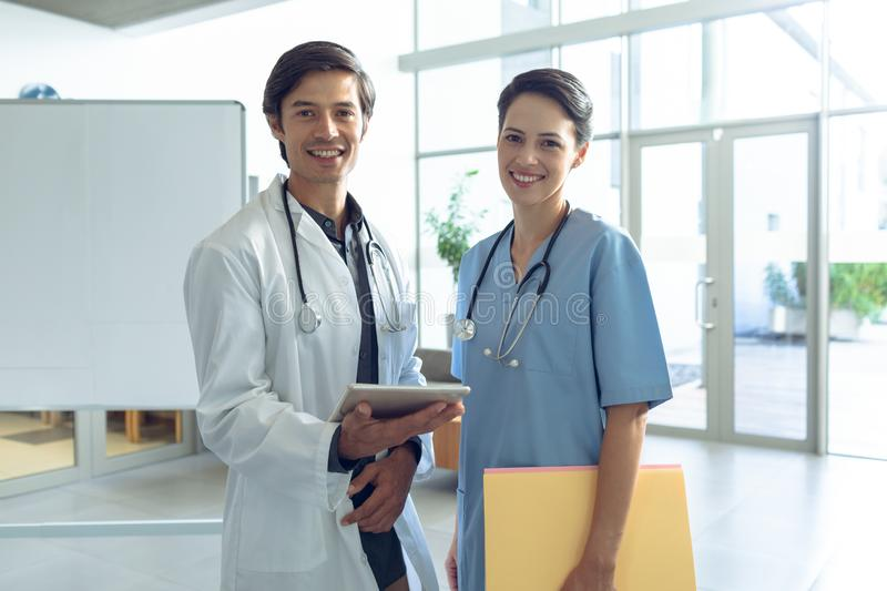 Male doctor and female nurse looking at camera in the lobby of hospital. Front view of happy male Caucasian doctor and female Caucasian nurse looking at camera stock photo
