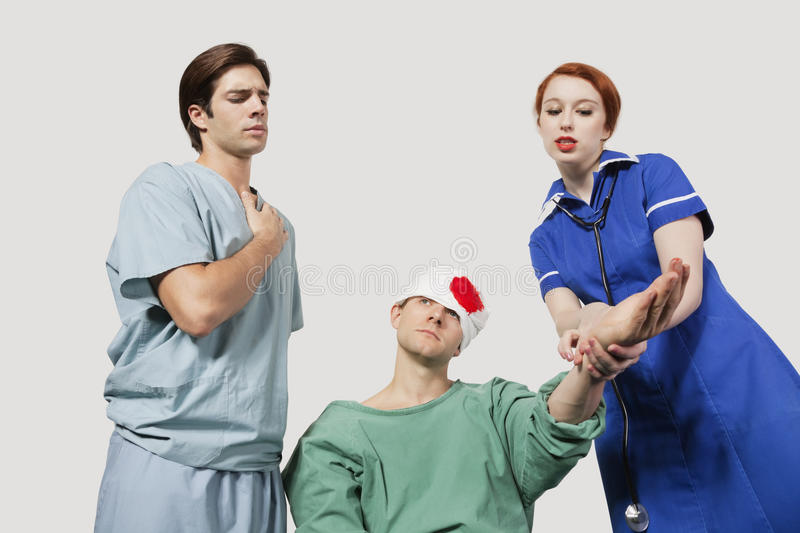 Male doctor with female nurse treating an injured patient against gray background royalty free stock photography