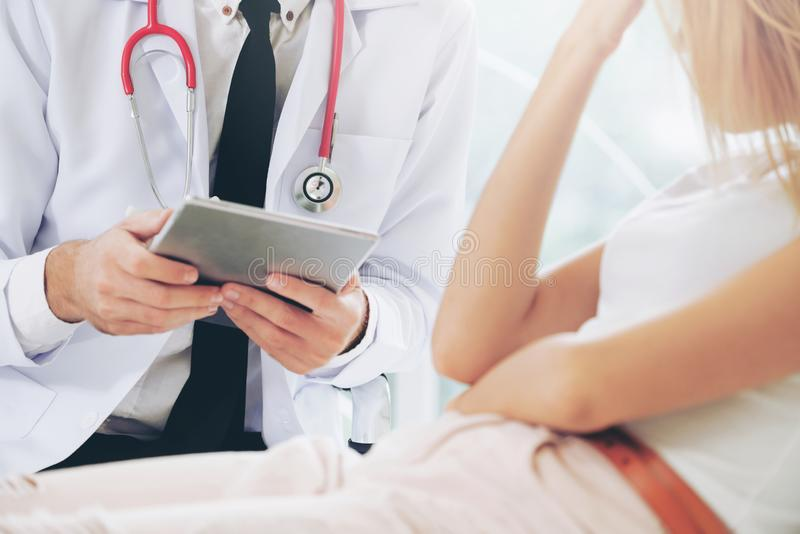 Male Doctor and Female Patient in Hospital Office stock photo