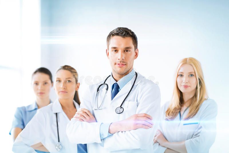 Male doctor in front of medical group. Attractive male doctor in front of medical group stock photo