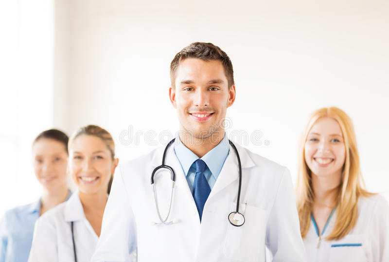 Male doctor in front of medical group. Attractive male doctor in front of medical group stock image