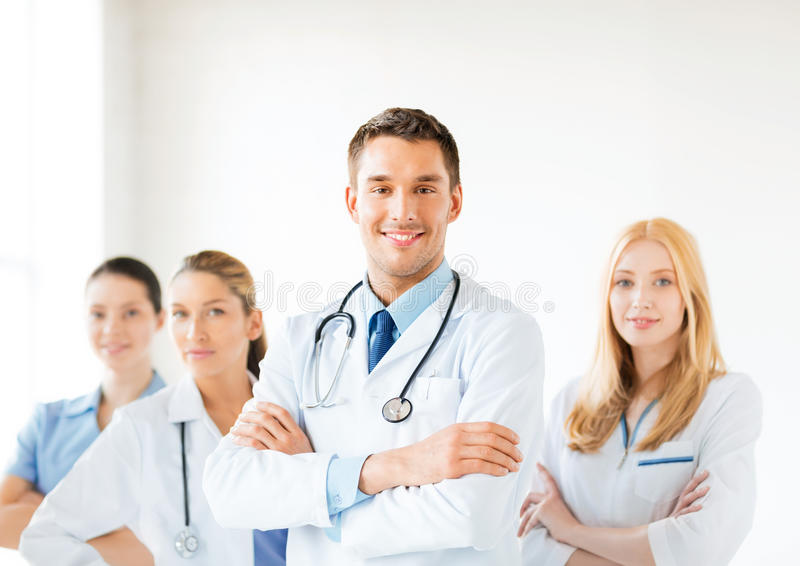Male doctor in front of medical group. Attractive male doctor in front of medical group royalty free stock photo