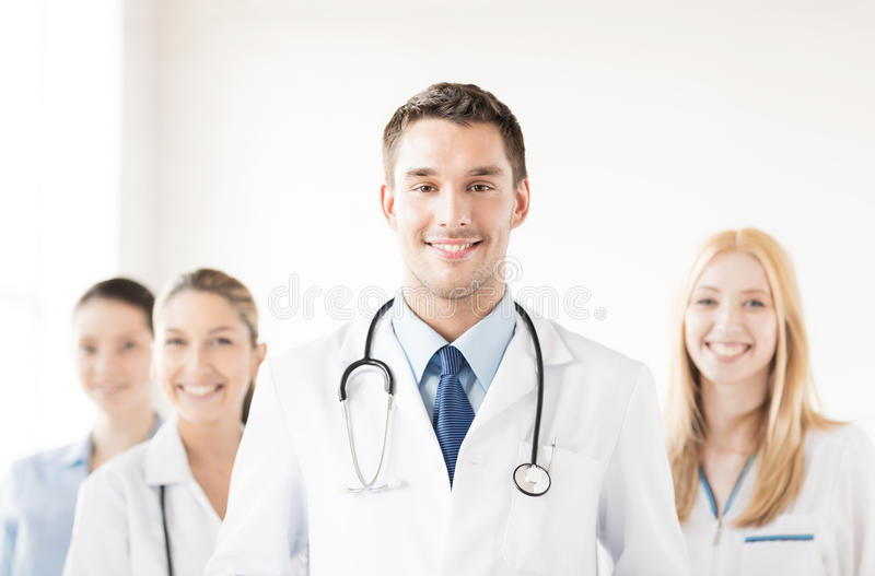 Male doctor in front of medical group. Attractive male doctor in front of medical group royalty free stock photography