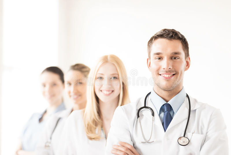 Male doctor in front of medical group. Attractive male doctor in front of medical group royalty free stock photos