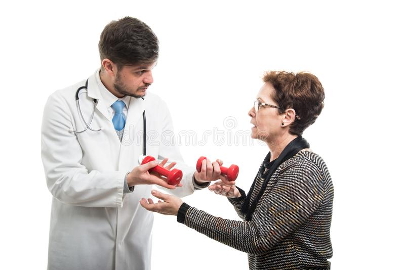 Male doctor giving red dumbbell to female senior patient stock photos