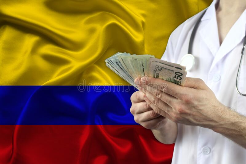 Male doctor holding a fan of dollars banknotes in his hands against the backdrop of the Colombia silk national flag, concept of. Health insurance, budget, cost stock photo