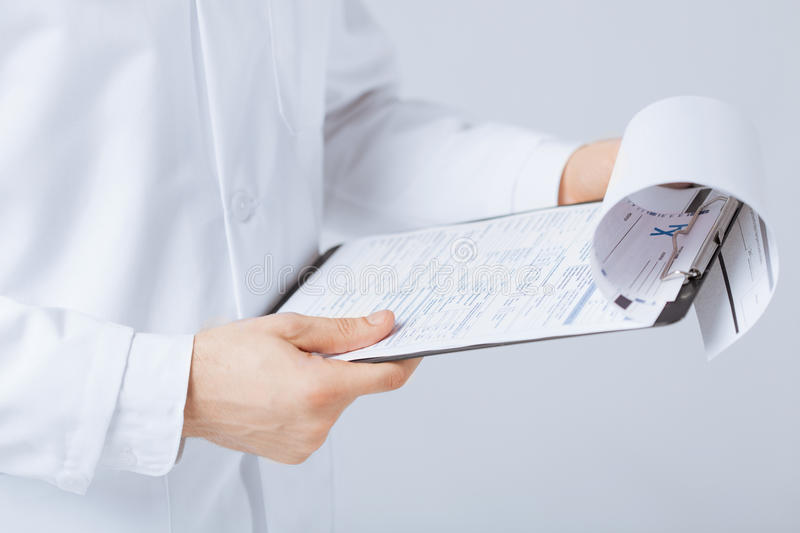 Male doctor holding prescription paper in hand