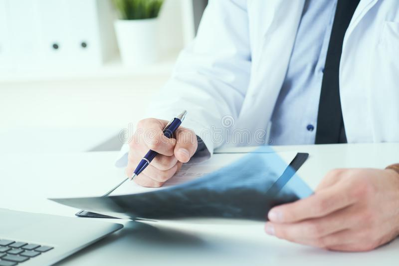 Close up of male doctor holding x-ray or roentgen image and making notes in medical form. Male doctor holding x-ray or roentgen image and making notes in stock photos