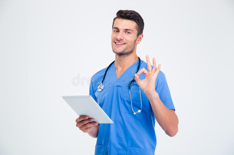 Male doctor holding tablet computer and showing ok sign stock photo
