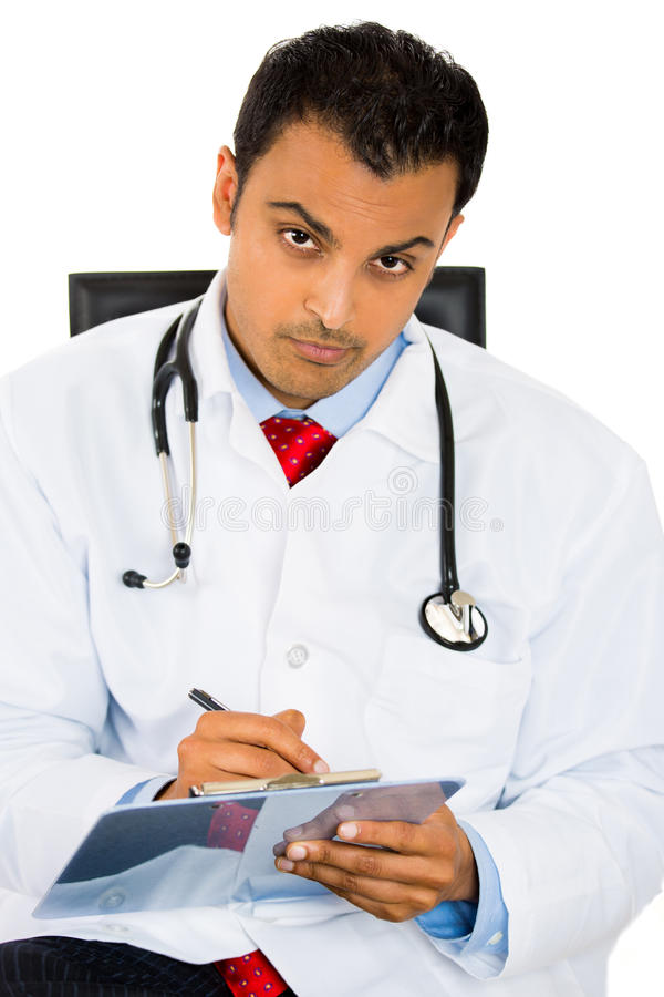 Download Male Doctor In Lab Coat Holding Reading Patients Chart While Sitting On A Chair Stock Photos - Image: 33170013