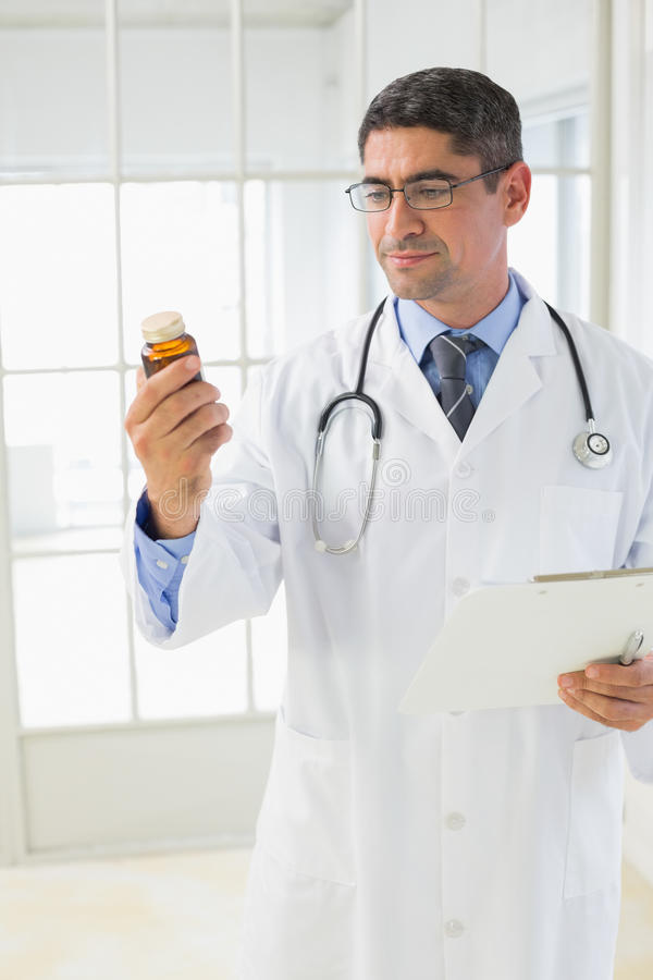Male doctor looking at a bottle of pills. In the hospital royalty free stock photos