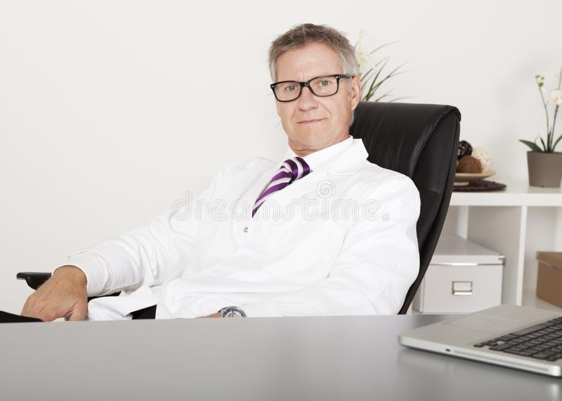 While Male Doctor Looking on Camera. While Sitting Down royalty free stock photos