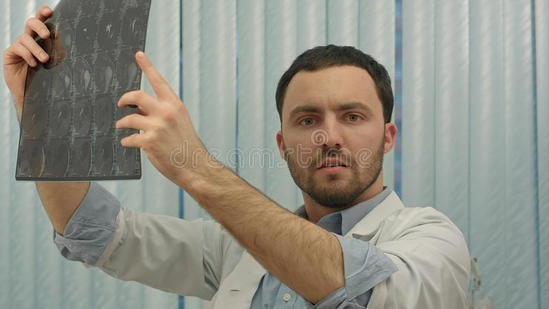 Male doctor looking with humorous shock at x ray. People. Professional shot in 4K resolution. You can use it e.g. in your commercial video, business stock photography