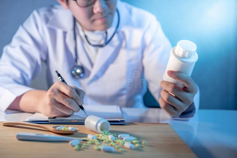 Male doctor looking at pill bottle working in hospital stock images