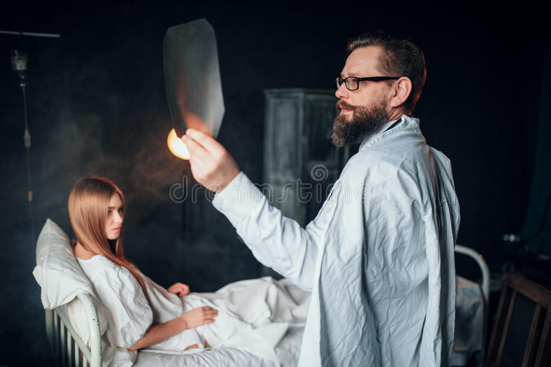 Male doctor looking at x-ray picture of sick woman stock image