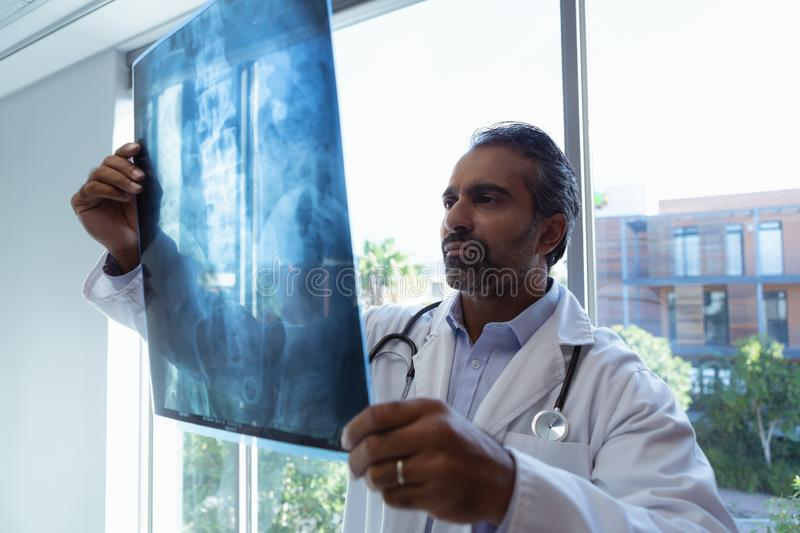 Male doctor looking at x-ray report in clinic at hospital. Front view of mature mixed race male doctor looking at x-ray report in clinic at hospital stock photos