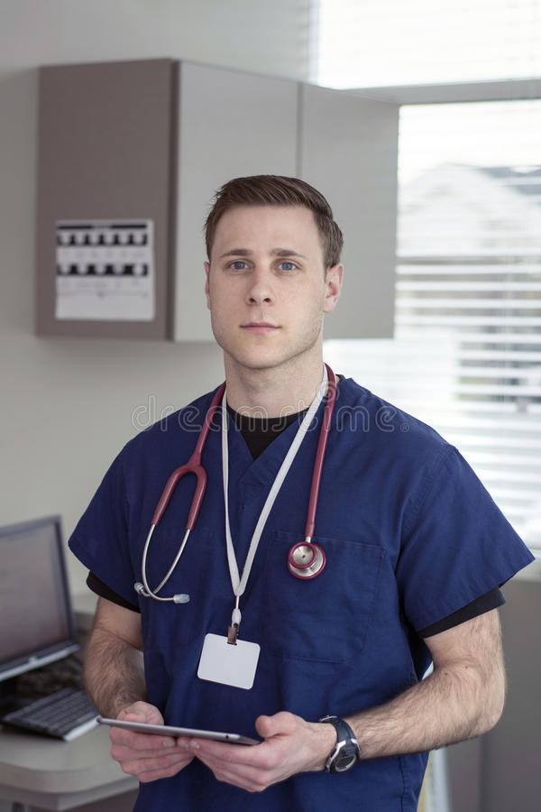Male doctor looking at tablet for medical information stock photography