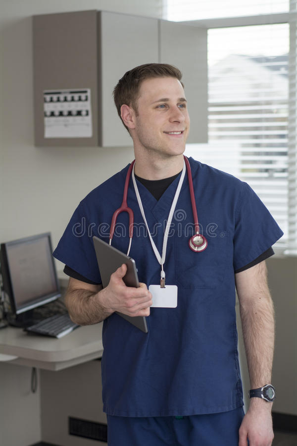 Male doctor looking at tablet for medical information stock photo