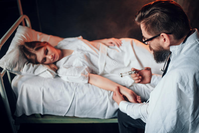 Male doctor makes syringe injection to sick woman stock image