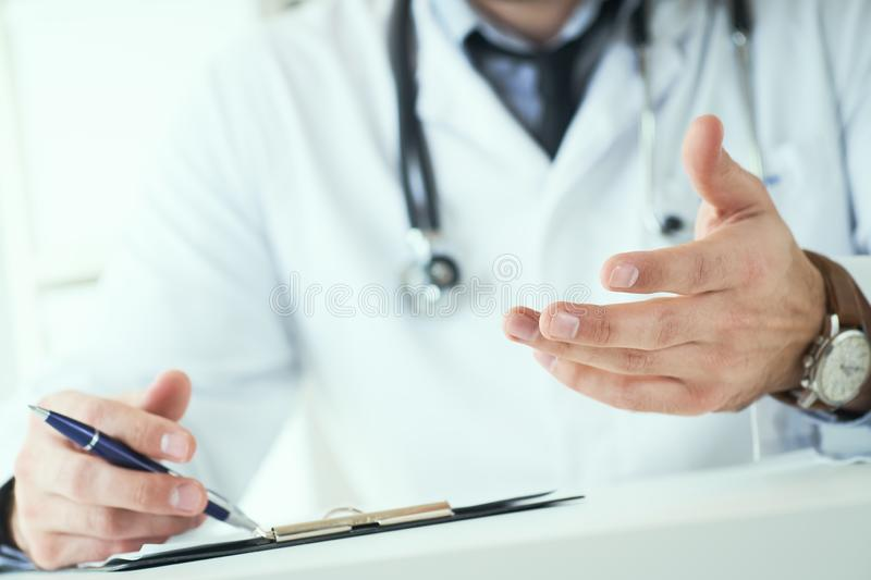 Male doctor making welcome gesture, politely inviting patient to sit down in medical office. Photo with depth of field. stock photo