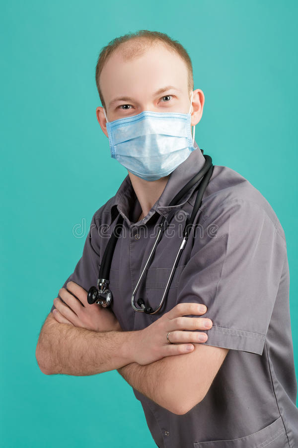 Male doctor in mask with stethoscope looking at camera on blue background stock photos