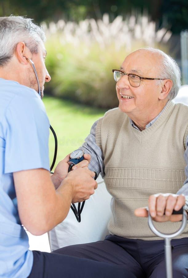 Male Doctor Measuring Blood Pressure Of Elderly stock photo