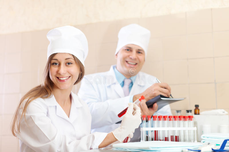 Male doctor and nurse makes blood test. Male doctor and nurse with test tubes makes blood test in medical laboratory royalty free stock photos