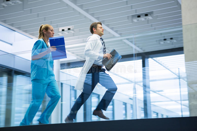 Male doctor and nurse running with x-ray report in corridor. At hospital royalty free stock photos