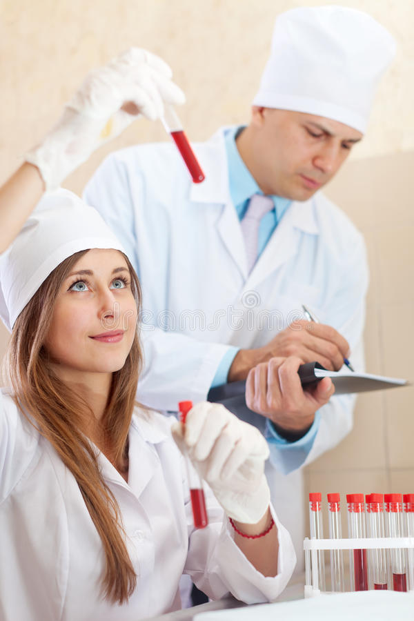 Male doctor and nurse with test tubes. Makes blood test in medical laboratory royalty free stock images