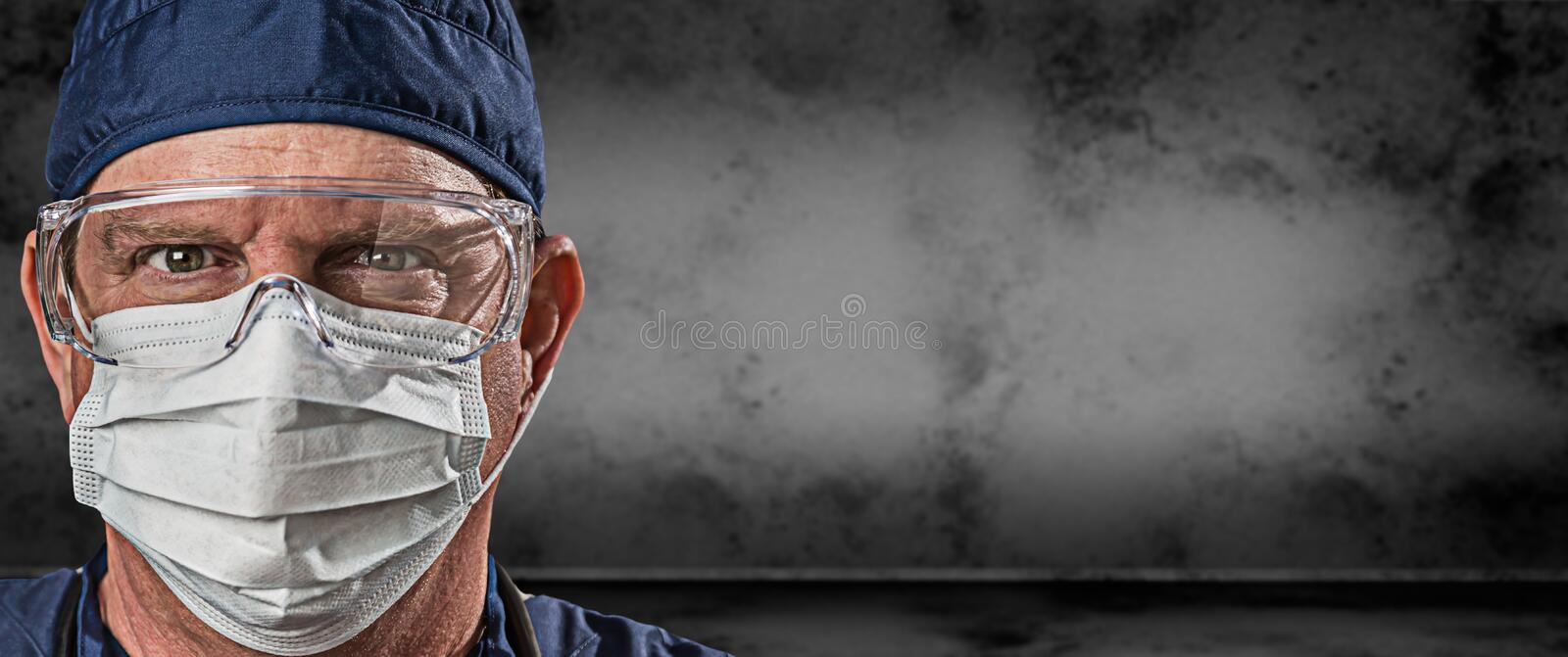Male Doctor or Nurse Wearing Goggles and Face Mask Against Grungy Dark Background Banner stock photography