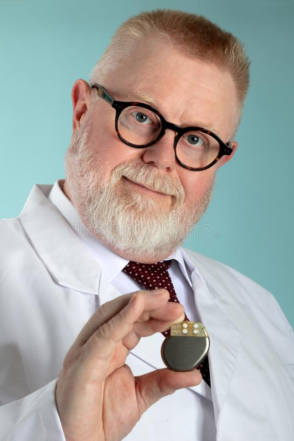 Male Doctor with Pacemaker. Male Doctor holding Pacemaker in front of camera with blue background stock photos