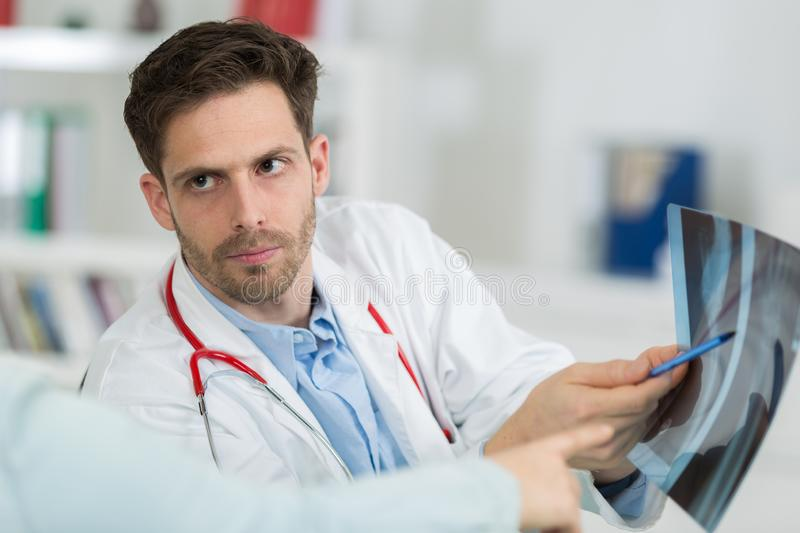 Male doctor with patient looking at x-ray at office royalty free stock images