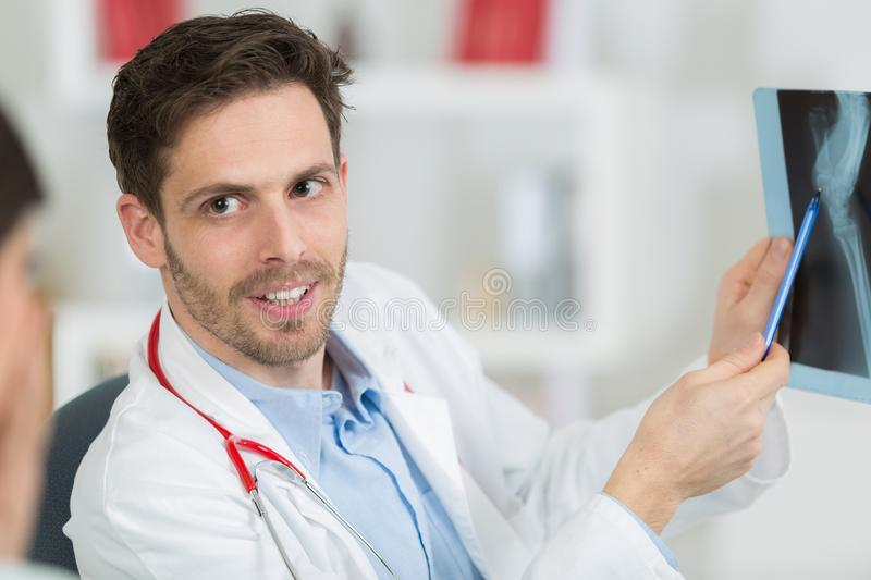 Male doctor with patient looking at x-ray at office royalty free stock photo