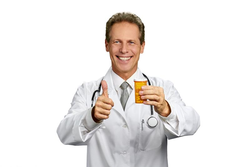 Male doctor with pills gesturing thumb up. stock image