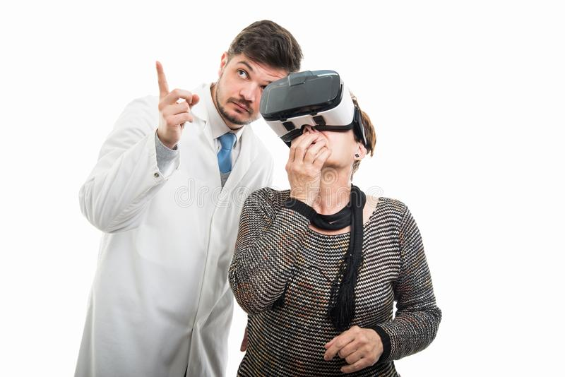 Male doctor pointing to female senior patient with vr goggles stock photo