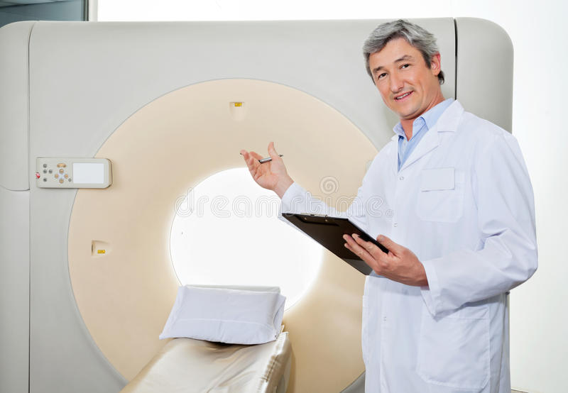 Male Doctor Presenting The CT Scan Machine stock photography