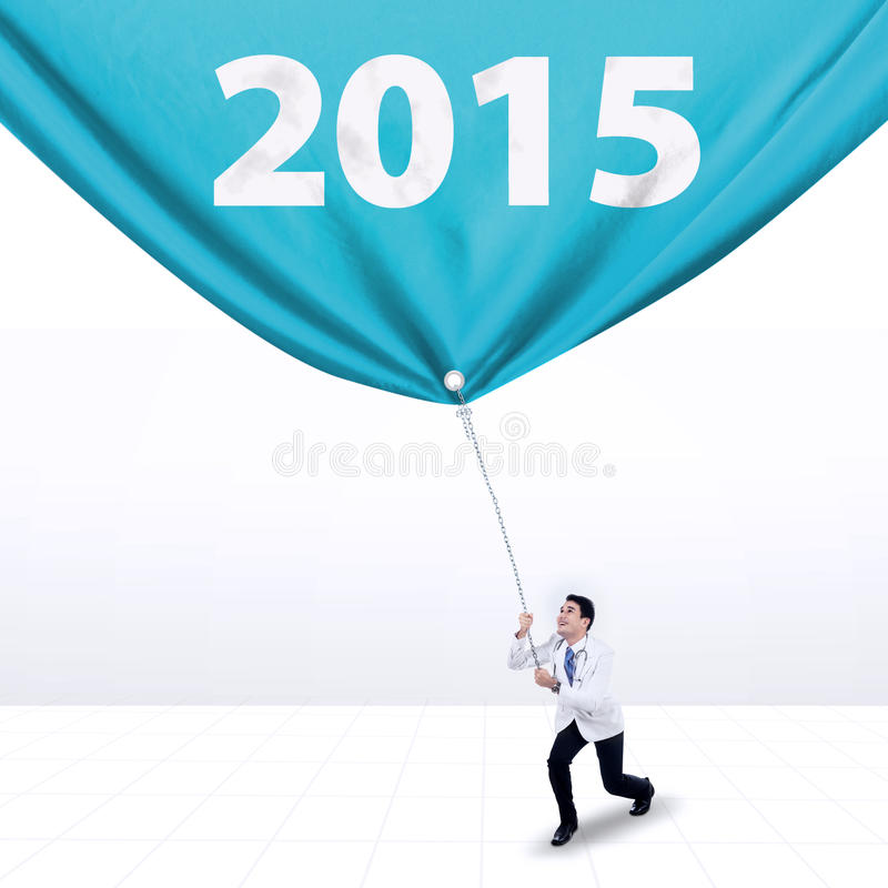 Male doctor pulling number 2015. Hispanic doctor dragging a big banner with number 2015, isolated over white background royalty free stock image