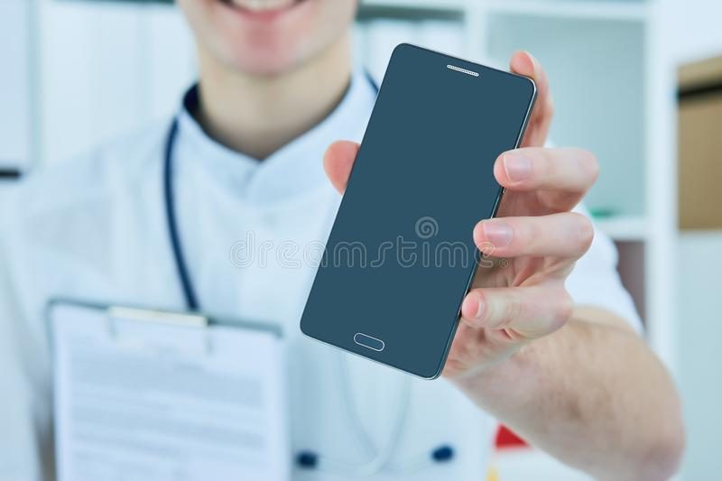 Male doctor`s hand showing a blank smart phone screen. royalty free stock image