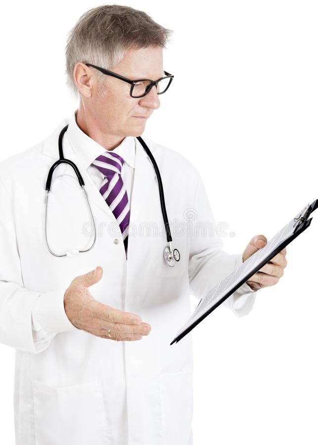Male Doctor Seriously Reading Medical Records royalty free stock image