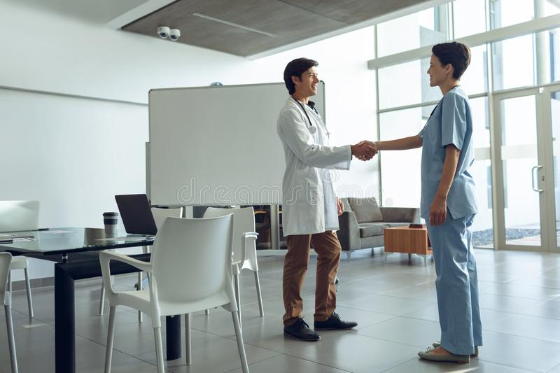 Male doctor shaking hands with female nurse in the hospital stock photo